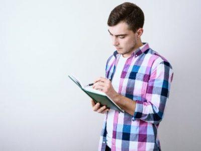 ノートにメモをとる男性